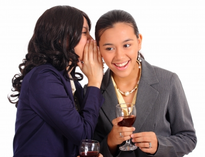 Yong girl whispering to her friend with wine glasses in girls hands